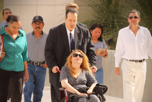 Leon Benzer, the mastermind of the scheme to take over and defraud HOAs, pushes a wheelchair of an unidentified woman while arriving for sentencing at Lloyd George United State Courthouse, Thursda ...