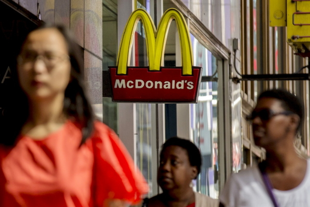 The sign for McDonald's in Times Square is seen as people pass by in New York July 23, 2015. McDonald's Corp's new chief executive expects global sales at established restaurants ...