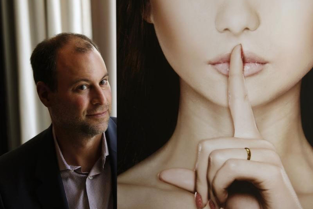 Ashley Madison founder Noel Biderman poses with a poster during an interview at a hotel in Hong Kong, Aug. 28, 2013. (Bobby Yip/Reuters)