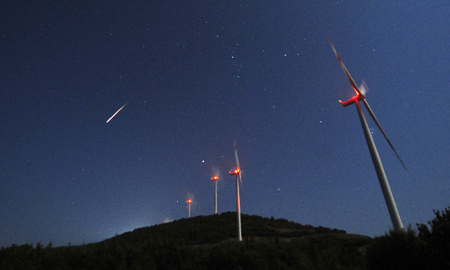 A meteor streaks across the sky during the Perseid meteor shower at a windmill farm near Bogdanci, south of Skopje, Aug. 13, 2014. (Ognen Teofilovski/Reuters)