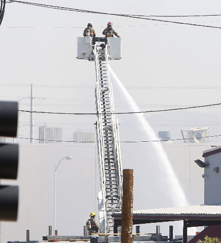 Firefighters spray water on a building after a propane tank explosion in the 4200 block of Polaris Avenue on Tuesday, Aug. 18, 2015. One person was transported to the hospital for burns. BIZUAYEHU ...