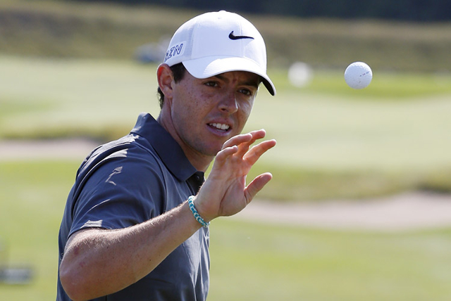 Rory McIlroy catches a golf ball on the practice range during a practice round for the 2015 PGA Championship golf tournament at Whistling Straits -The Straits Course. Mandatory Credit: Brian Spurl ...
