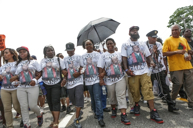 Members of the community, including family members of the late Michael Brown, join together on August 9, 2015, for a march through Ferguson, Missouri, including a stop at the memorial for Michael  ...
