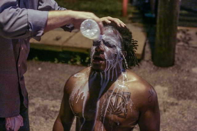 A protester in Ferguson, Missouri Sunday night, August 9, 2015 is doused in a milky white solution to ease the pain after the introduction of pepper spray during a protest. It is unclear who intro ...