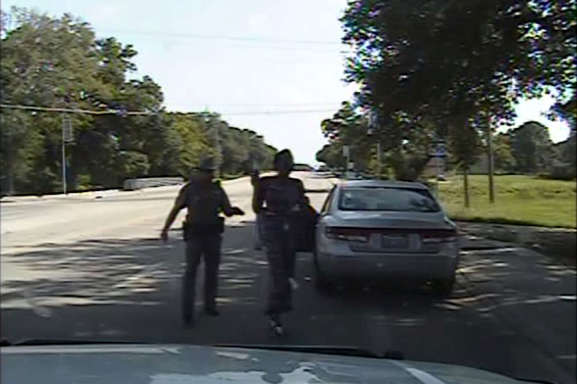 A Waller County Department of Public Safety officer points a Taser as he orders Sandra Bland out of her vehicle, in this still image captured from the police dash camera video from the traffic sto ...