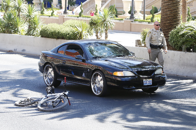 A Las vegas police officer investigates a crash that sent a bicyclist to the hospital with life-threatening injuries on the Las Vegas Strip near Spring Mountain Road on Monday morning, Aug. 3, 201 ...