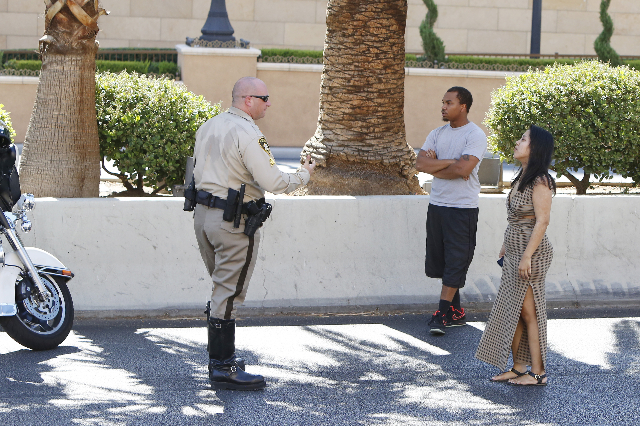 A Las vegas police officer talks to a driver, right, of a car involved in a crash that sent a male bicyclist to the hospital with life-threatening injuries on the Las Vegas Strip near Spring Mount ...