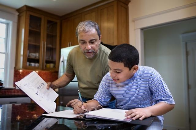 Grandfather helping boy with homework (Thinkstock)