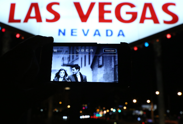 "The logo of car-sharing service app Uber is seen on a smartphone as it was photographed in front of the iconic ""Welcome to Fabulous Las Vegas"" sign Wednessday, May 6, 2015. (Bizuayehu Tesfaye/ ..."