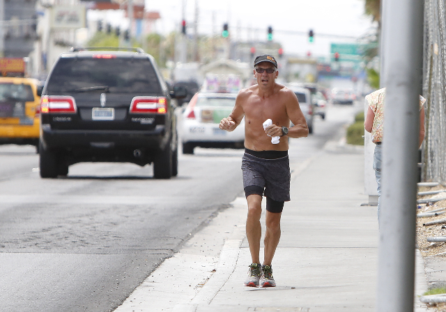 A man jogs on a cloudy day on Paradise Rd. near Howard Hughes Pkwy., on Thursday, July 9, 2015. Temperatures will drop significantly to 10 degrees below normal — predicted at 94 degrees — as a ...