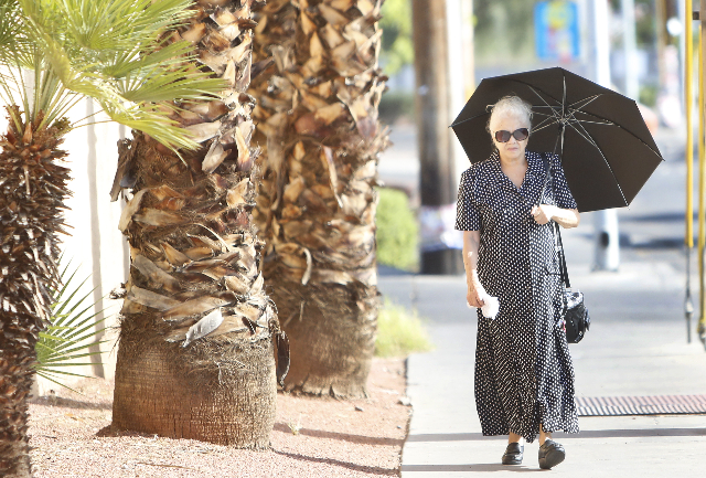 A woman holds her umbrella to protect herself from sun as she walks near Bonanza Rd. and Bruce St., on Friday, July 10, 2015. After a week of temperatures cooler than normal, things will start to  ...