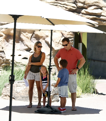 Justin Henderson, right, his son Julian (6), second right, his daughter Savana (4) and his wife Candice, all of Austin, Texas stand on a hot day under a huge umbrella as they visit the Springs Pre ...