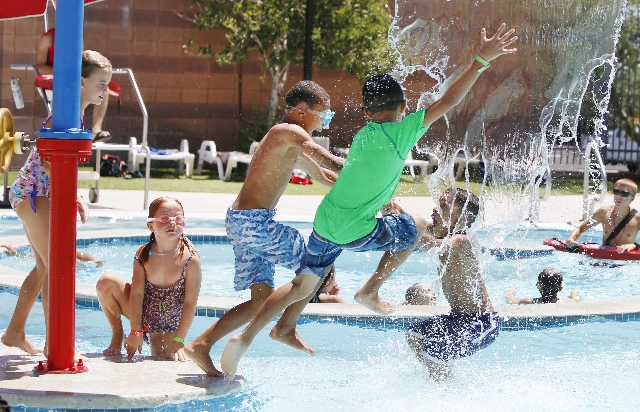 Children including Emma Ambrose (8), left, and Heath Shim (9), second right, play on a hot day at the YMCA pool on 4141 Meadows Ln in Las Vegas on Tuesday, Aug. 4, 2015. (Bizuayehu Tesfaye/Las Veg ...
