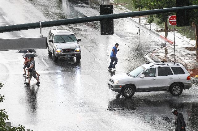 People walk along 3rd Street at Bonneville Avenue as heavy rain falls in downtown Las Vegas on Thursday, Aug. 8, 2015. CHASE STEVENS/LAS VEGAS REVIEW-JOURNAL Follow him @csstevensphoto