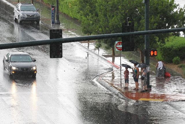 People holding umbrellas wait to cross the street as heavy rain falls in downtown Las Vegas on Thursday, Aug. 8, 2015. CHASE STEVENS/LAS VEGAS REVIEW-JOURNAL Follow him @csstevensphoto