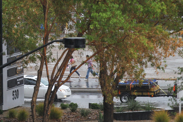 People run along Las Vegas Boulevard as heavy rain falls in downtown Las Vegas on Thursday, Aug. 8, 2015. CHASE STEVENS/LAS VEGAS REVIEW-JOURNAL Follow him @csstevensphoto