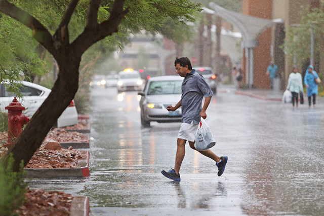 A shopper gets caught in the rain while running to the parking lot at Las Vegas South Premium Outlets located at 7400 S. Las Vegas Blvd. Saturday, Aug. 1, 2015. (Ronda Churchill/Las Vegas Review-J ...