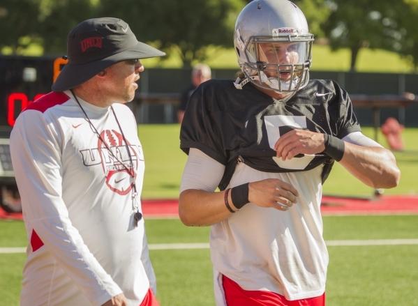 UNLV football coach Tony Sanchez, left, talks to quarterback Blake Decker during practice Aug. 10 at Rebel Park. The senior has secured the starting job.  (Jeff Scheid/Las Vegas Review-Journal)