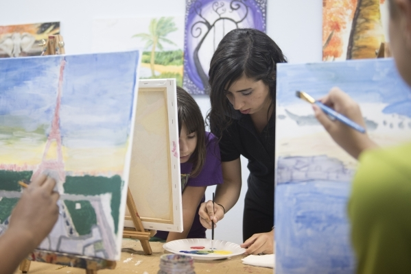 Nine-year-old student Emily Parkes, left, is given instruction by Vanessa Torres during the group painting class at The King Art Studio in Henderson, Wednesday, Aug. 19, 2015. (Jason Ogulnik/Las V ...