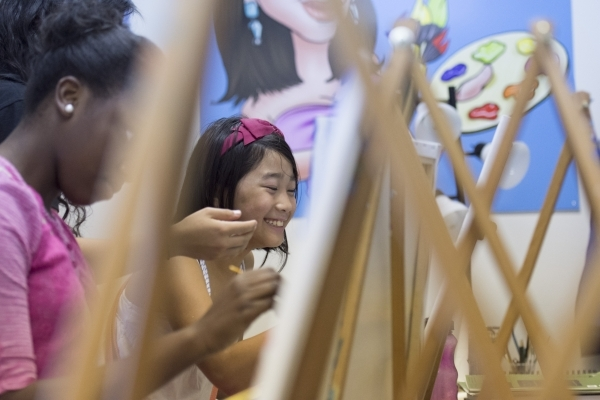Ten-year-old Justine Retodo, right, and 11-year-old Torryana Tanis work on their pieces during the group painting class at The King Art Studio in Henderson, Wednesday, Aug. 19, 2015. (Jason Ogulni ...