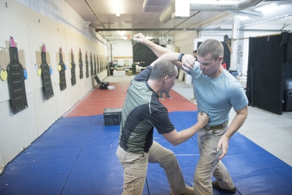 Dave Koopman, left, and John Ivens demonstrate hand-to-hand combat techniques during The Bodyguard Adventure course at Vegas Tactical Adventures in North Las Vegas, Aug. 18. (Jason Ogulnik/View)