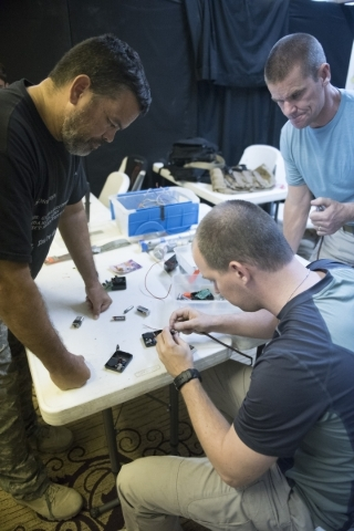 From left, Willson Warner, Dave Koopman and John Ivens build improvised explosive devices so that they can better understand how they work during The Bodyguard Adventure course at Vegas Tactical A ...