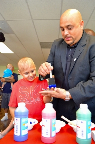 Henderson Hyundai general manager Rob Mirra paints the hand of Children's Specialty Center of Nevada patient Ian Heath during the presentation of a $50,000 Hyundai Hope on Wheels Impact Awar ...