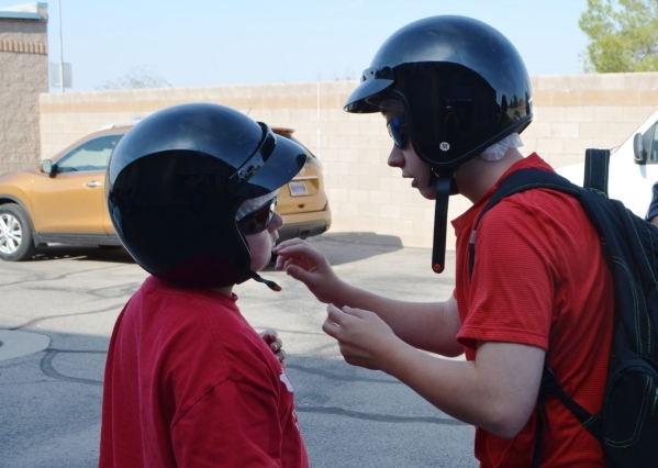 MacKenzie Legault, 14, helps his brother Breandan, 11, with his helmet in preparation for a Vegas Trikes tour. (Ginger Meurer/Special to View)