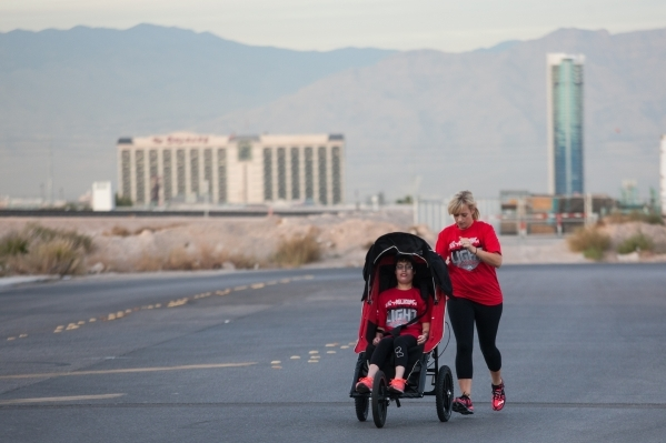 Eden Capsouto pushes her daughter Taylor Little, now 22 and who has cerebral palsy, in a jogging stroller in preparation for the Rock 'n' Roll Las Vegas Half-Marathon in 2013. Eden and ...