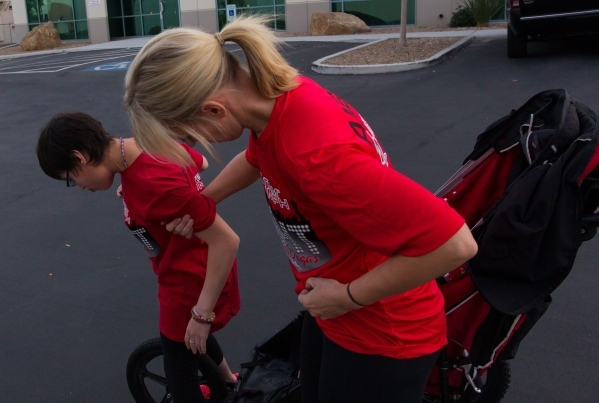 Eden Capsouto helps her daughter, Taylor Little, out of a jogging stroller after a run in preparation for the Rock 'n' Roll Las Vegas Half-Marathon  in 2013. (Chase Stevens/View file p ...