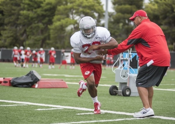 UNLV running back Keith Whitely (28) takes a fake hand off from running backs coach Jaime Christian during practice at Rebel Park on the UNLV campus on Tuesday, Aug. 25, 2015. Martin S. Fuentes/La ...
