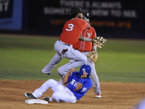 El Paso Chihuahuas shortstop Hector Gomez turns a double play as Las Vegas 51s baserunner Josh Rodriguez slides into second base in the fifth inning of their Triple-A minor league baseball game at ...