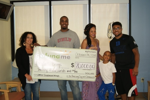 Former Bishop Gorman High star and now Duke senior running back Shaquille Powell, right, helps hold up a check that went to helping defray the medical costs for his brother Malachi Briggs' f ...