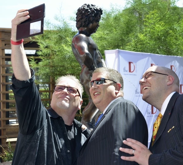 "Derek Stevens, co-owner of the D hotel-casino, center, takes a picture with Kevin Burke, left, and Adam London during an unveiling event for a statue called ""Manneken Pis,"" Dutch for &qu ..."