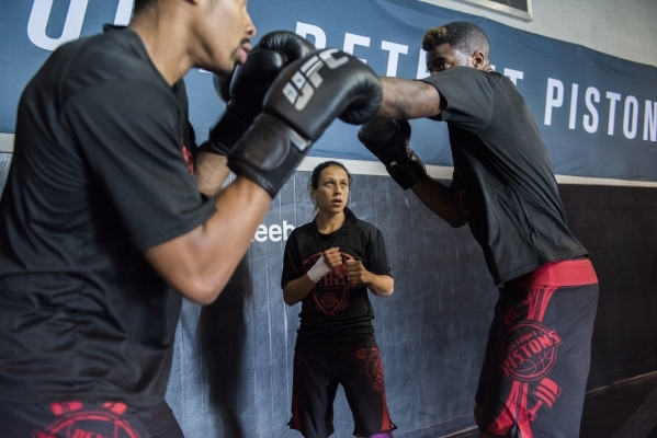 UFC women's strawweight champion Joanna Jedrzejczyk, center, holds a training session with NBA basketball players, from left, Spencer Dinwiddie and Reggie Bullock of the Detroit Pistons at t ...