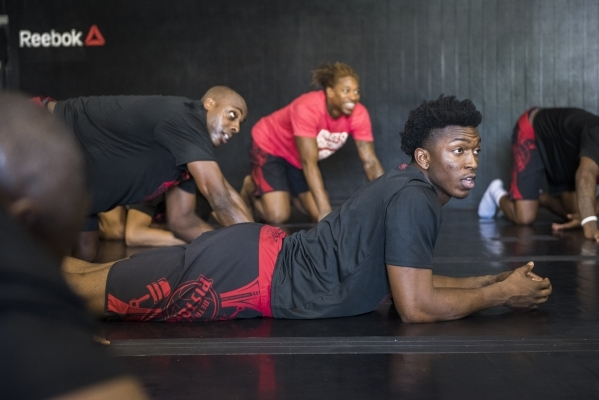 NBA basketball player Stanley Johnson from the Detroit Pistons does some light stretching during a training session with UFC fighters from the UFC gym in Las Vegas on Wednesday, Sept. 2, 2015. (Ma ...