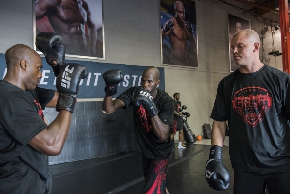 UFC heavyweight fighter Stefen Struve, right, holds a training session with NBA basketball players, from left, Anthony Tolliver and Joel Anthony of the Detroit Pistons at the UFC gym in Las Vegas  ...