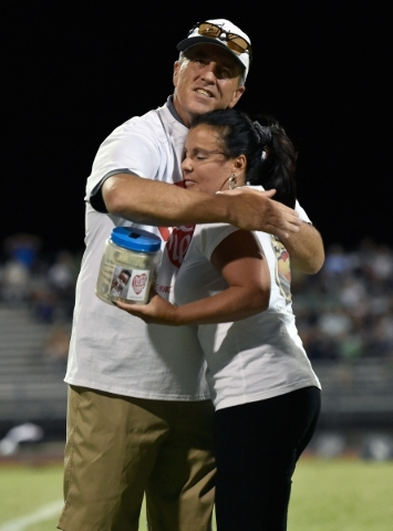 Jessica Langgin, right, of OfficerDown.us gets a hug from Green Valley High School vice principal John Scott after she accepts $1,665 that was collected during the Las Vegas and Green Valley high  ...