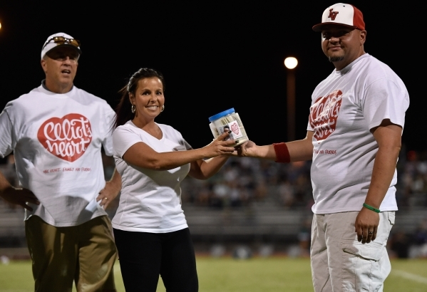 Jessica Langgin, center, of OfficerDown.us accepts a donation of $1,665 from Las Vegas High School football coach Cody Prichett, right, collected at the Las Vegas-Green Valley football game at Las ...
