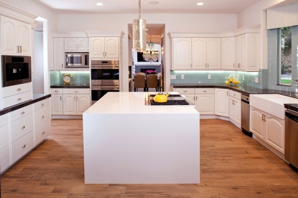 A kitchen where white quartz is used on the island and gray marble.