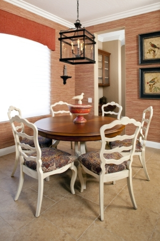 A breakfast room where red grass cloth is used for wallpaper.