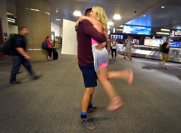 Emmy Barling, right, greets her Marine boyfriend, Eric Perez, as he arrives in the baggage claim area at McCarran International Airport on Friday, Sept. 4, 2015, in Las Vegas. Perez is on leave fo ...