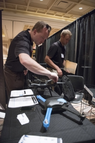 Nevada Dynamics employees CEO MacCallister Higgins, left, and President Erik Edgington set up their Reno-based start-up's display at InterDrone in the convention center at the Rio hotel-casi ...