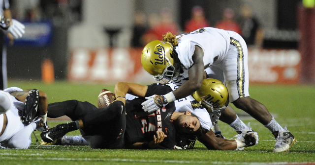 UNLV Rebels quarterback Kurt Palandech, center, loses his helmet as he is tackled by UCLA Bruins linebackers Jayon Brown (12) and  Kenny Young (42) in the second quarter at Sam Boyd Stadium Saturd ...