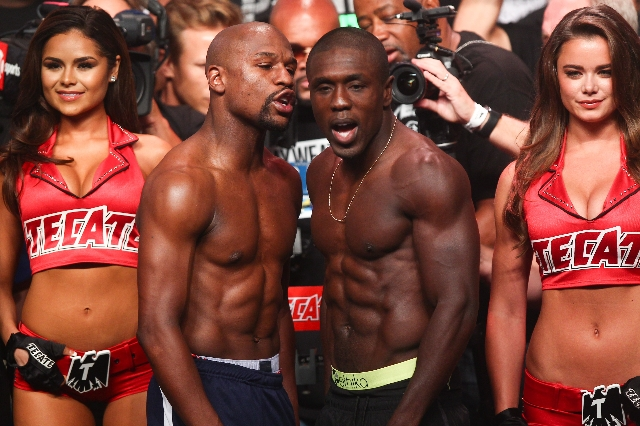Boxers Floyd Mayweather Jr., left, and Andre Berto exchange words while posing for a photo ahead of their Sept. 12 fight during the weigh-in event at the MGM Grand Garden Arena in Las Vegas on Fri ...