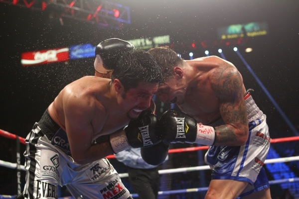 Jhonny Gonzalez, left, and Jonathan Oquendo trade punches during their super featherweight boxing match at the MGM Grand Garden Arena in Las Vegas on Saturday, Sept. 12, 2015. Chase Stevens/Las Ve ...
