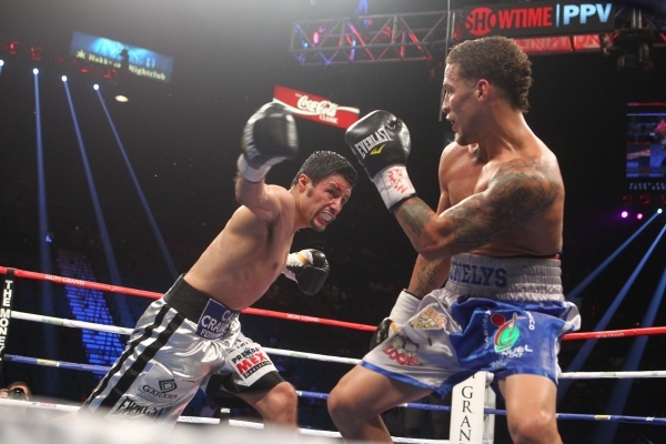 Jhonny Gonzalez, left, throws a right at Jonathan Oquendo during their super featherweight boxing match at the MGM Grand Garden Arena in Las Vegas on Saturday, Sept. 12, 2015. Chase Stevens/Las Ve ...
