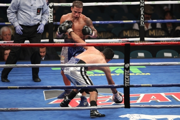 Jonathan Oquendo, left, looks as his opponent Jhonny Gonzalez sleeps in their super feather weight bout at MGM Grand Garden Arena in Las Vegas Saturday, Sept. 12, 2015. Oquendo won by a split deci ...
