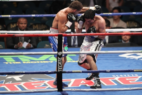 Jonathan Oquendo, left, throws a punch against Jhonny Gonzalez in their super feather weight bout at MGM Grand Garden Arena in Las Vegas Saturday, Sept. 12, 2015. Oquendo won by a split decision.  ...