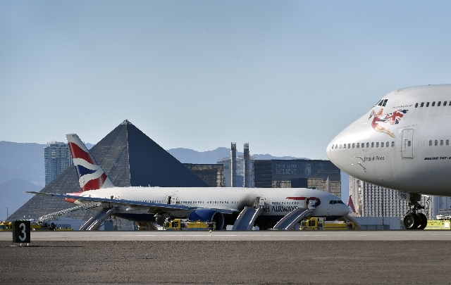 The tip of a Virgin Atlantic jumbo jet passes in front of a British Airways passenger jet that is parked on the runway after an onboard fire broken out at McCarran International Airport on Tuesday ...